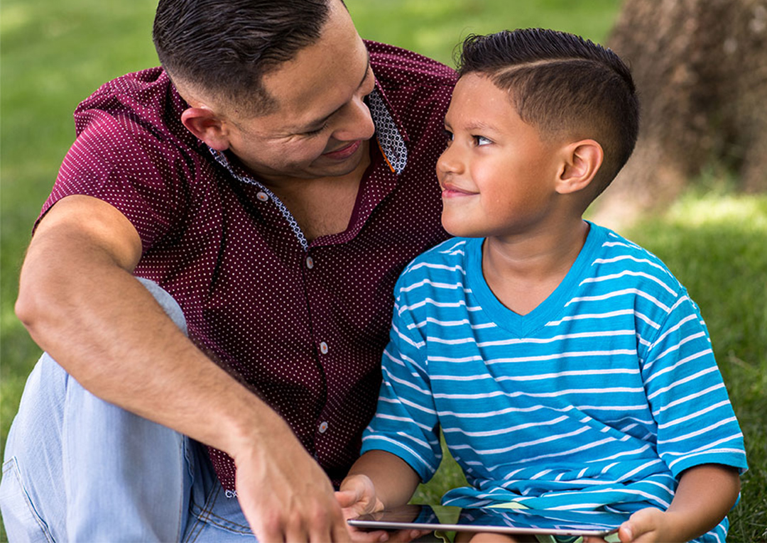 Father and son playing on tablet