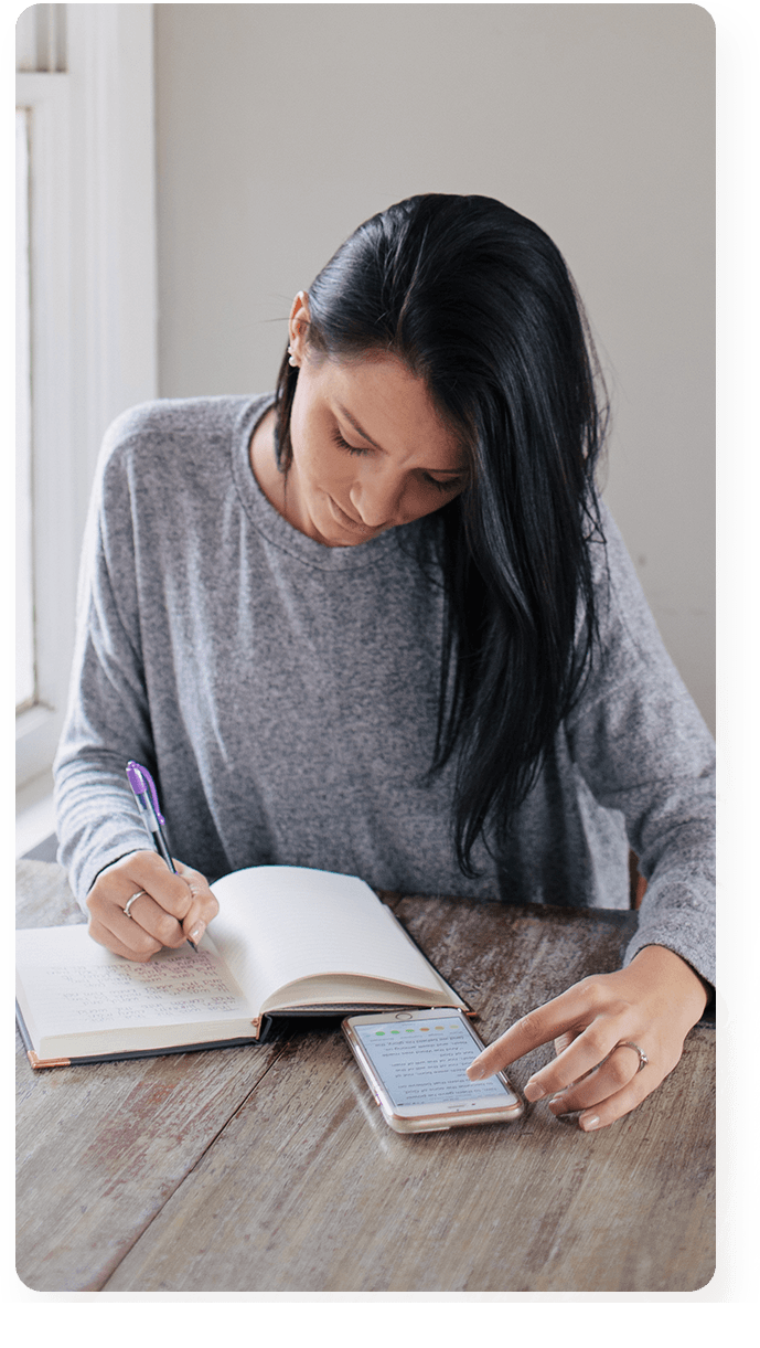 Woman journaling while reading Bible on phone