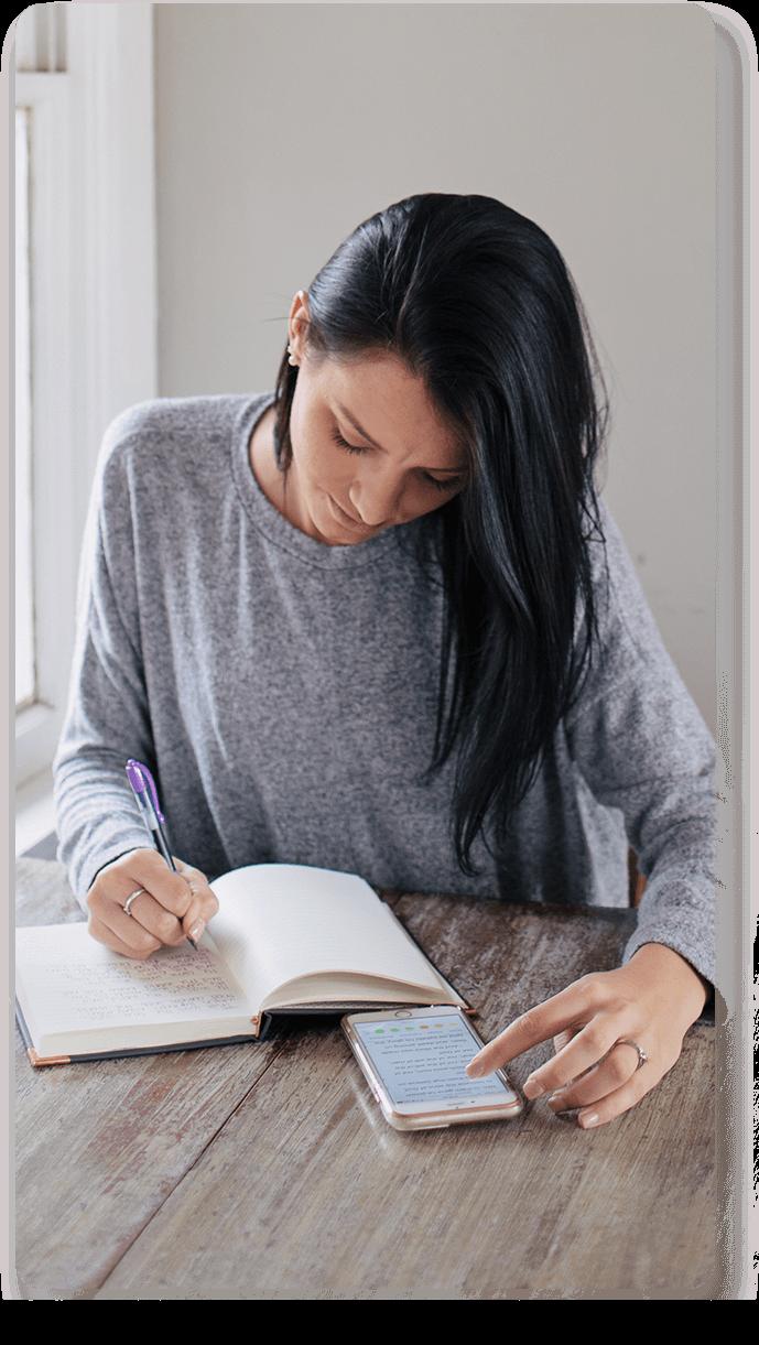 Mujer llevando su diario mientras lee la Biblia en el celular
