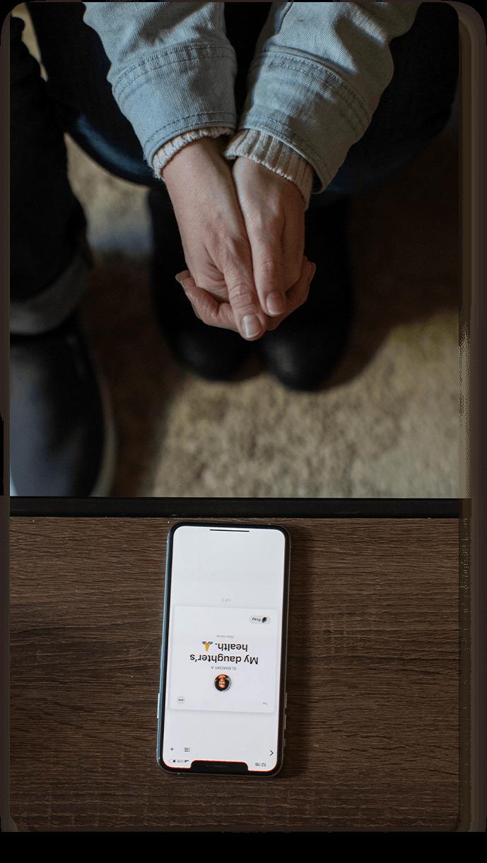 Persona orando con la Biblia App abierta en el celular