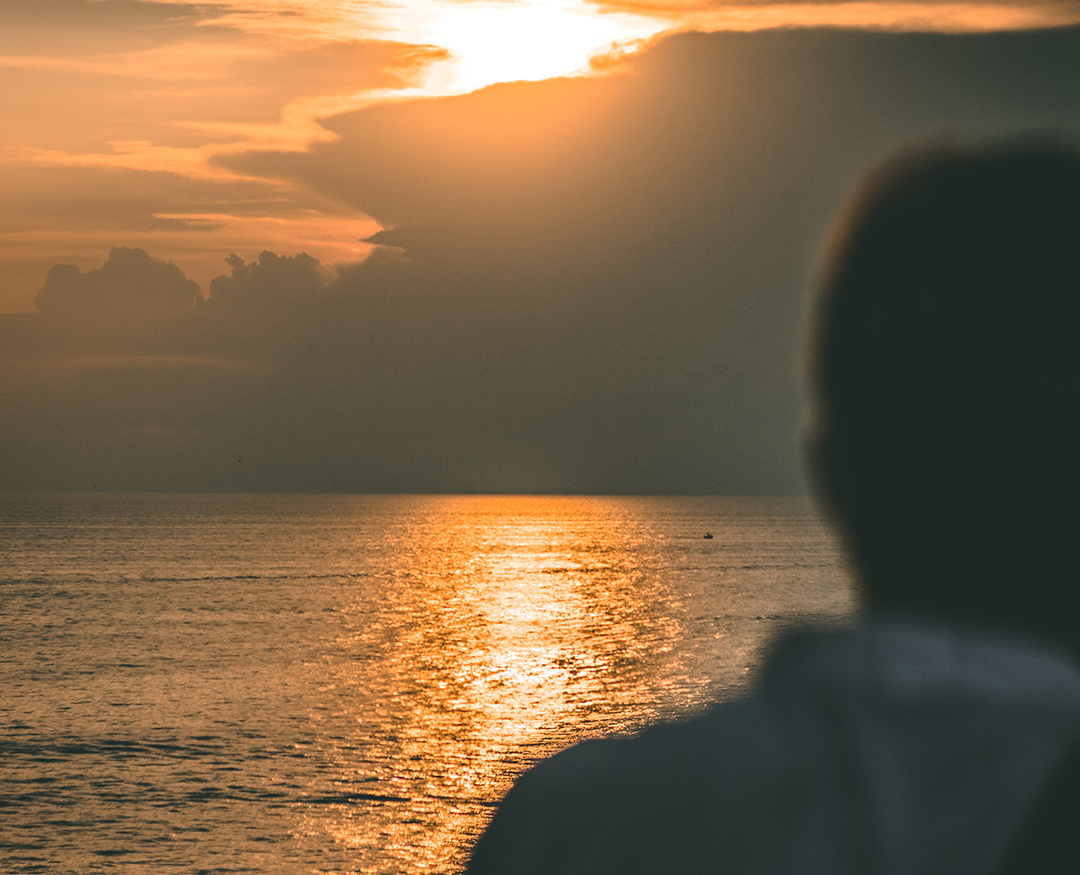 Silhouette of person looking at sunset over water