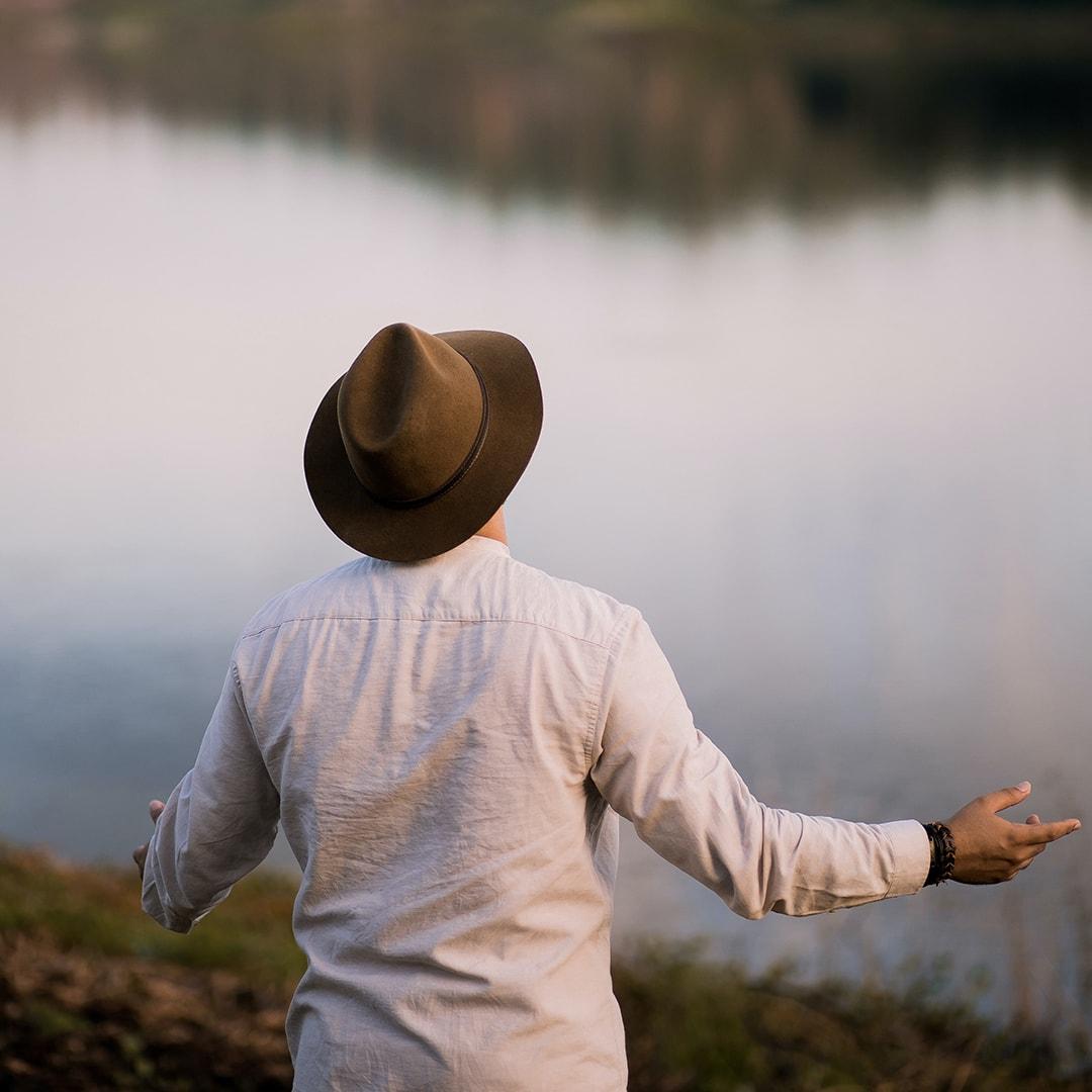 Pessoa orando próxima a um lago