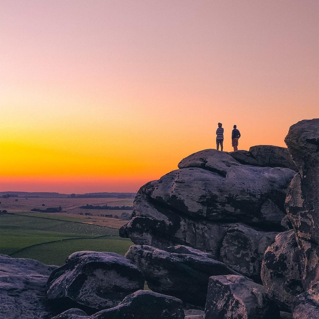 站在岩石上看日落的人